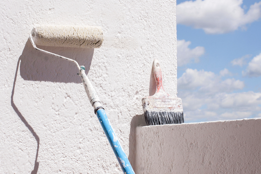 Paint brush and roller against wall